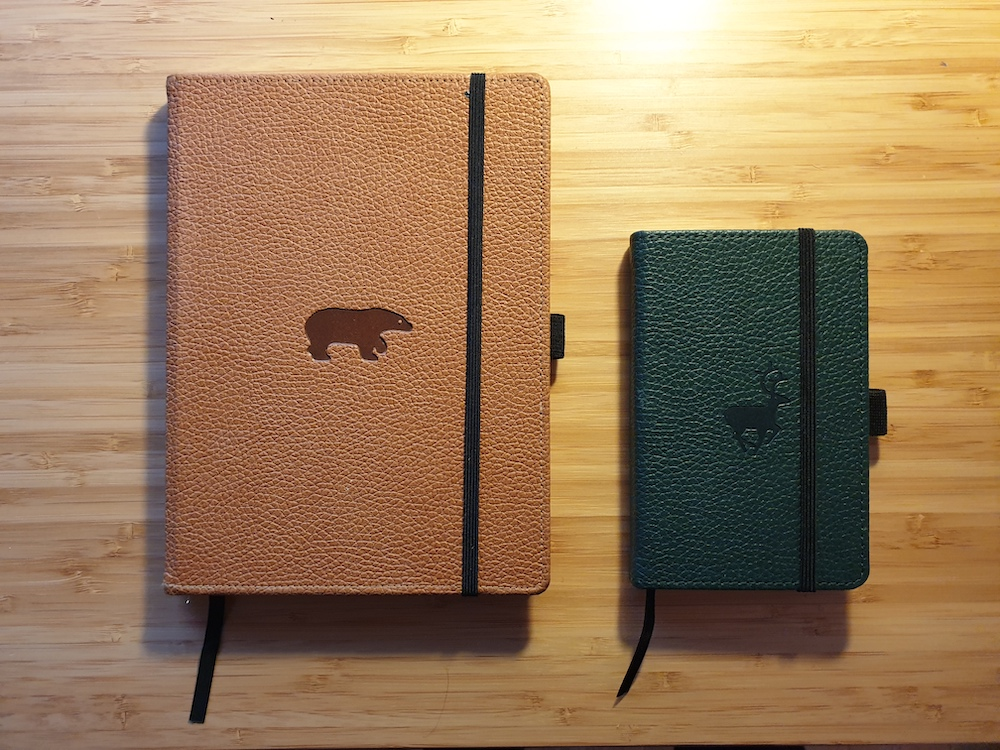 Notebooks on desk. On the left: Camel brown notebook with bear symbol on cover. On the right: Forest green notebook with deer symbol on cover.